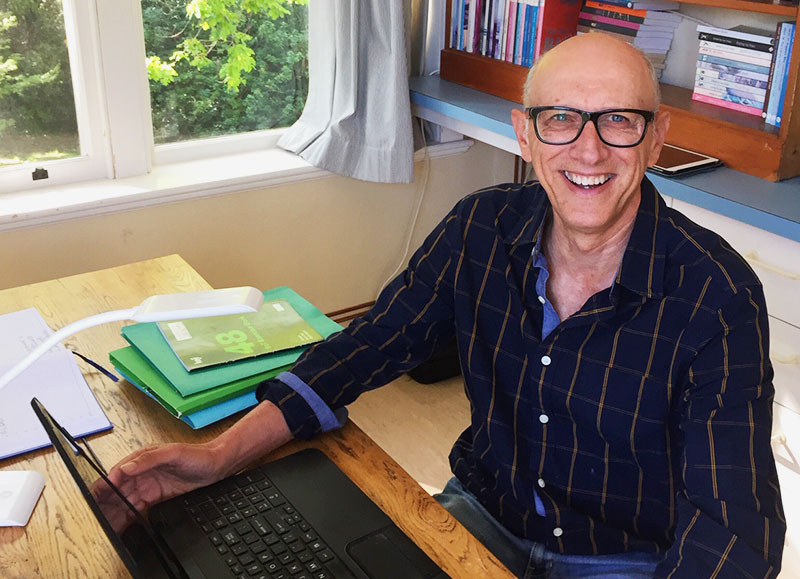 Greg Woodland wearing glasses at desk with laptop and bookshelf