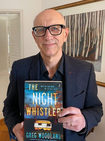 Greg Woodland wearing glasses holding book The Night Whistler
